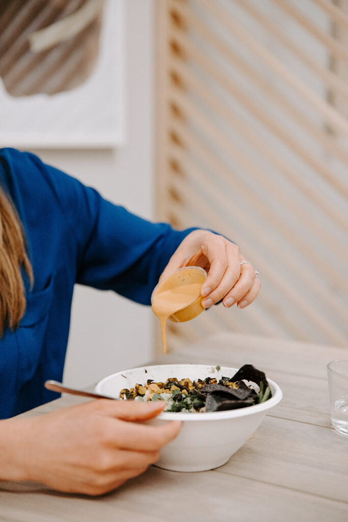 A woman in a blue shirt sitting at a table pouring dressing on her salad.