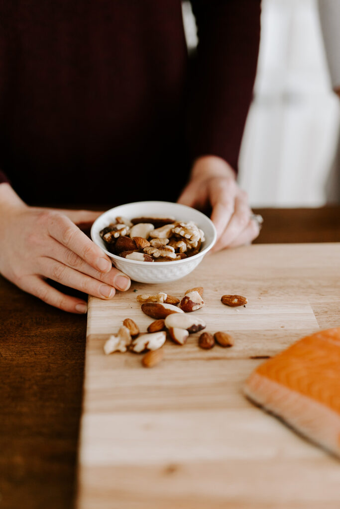 woman holding a small bowl of walnuts to boost your mood