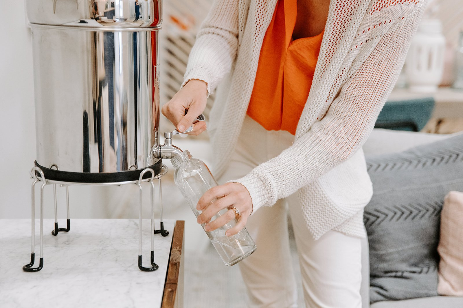 A woman in a white sweater fills her glass water bottle from a Berkey filter.