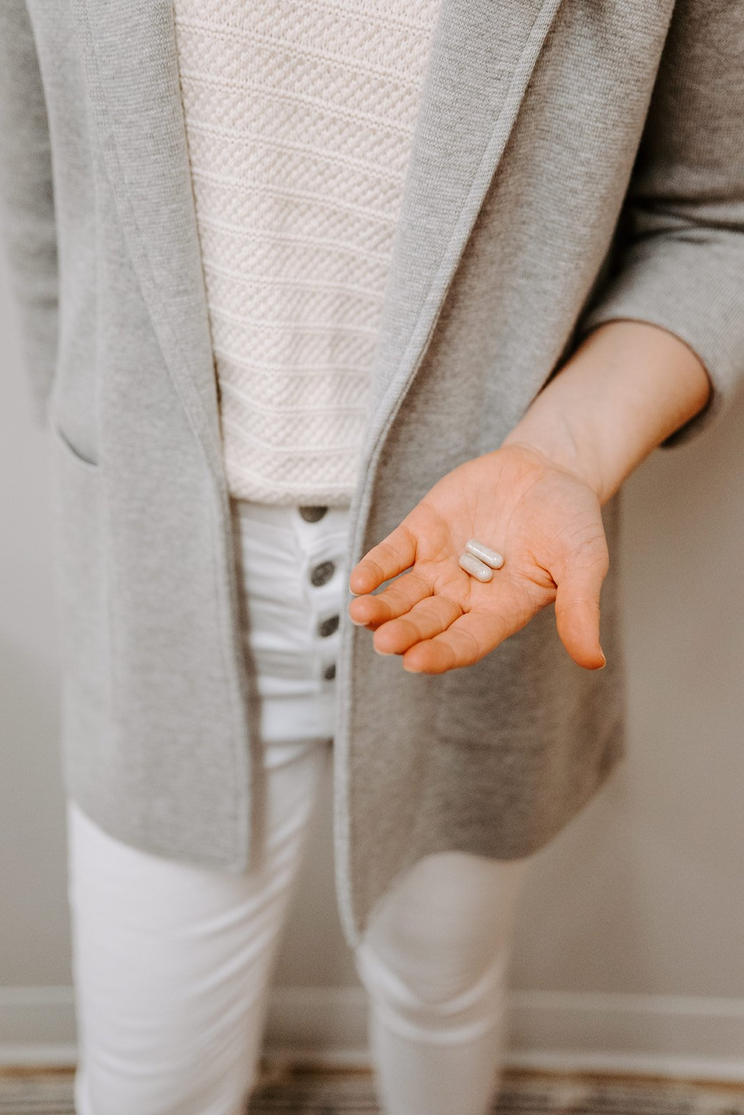 A woman in a gray seater blazer holds two small pills in her open hand.